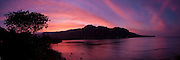 A panoramic of a dramatic sunset sky reflects on Kahana Bay on Oahu's windward coast in Hawaii