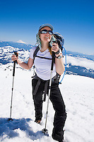 A 40's Caucasian woman hikes up the Muir snow field on Mt. Rainier with Mt. Adams and the Tatoosh range in the distance behind her.