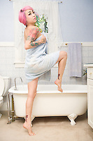 Young woman in towel posing in front of bathtub