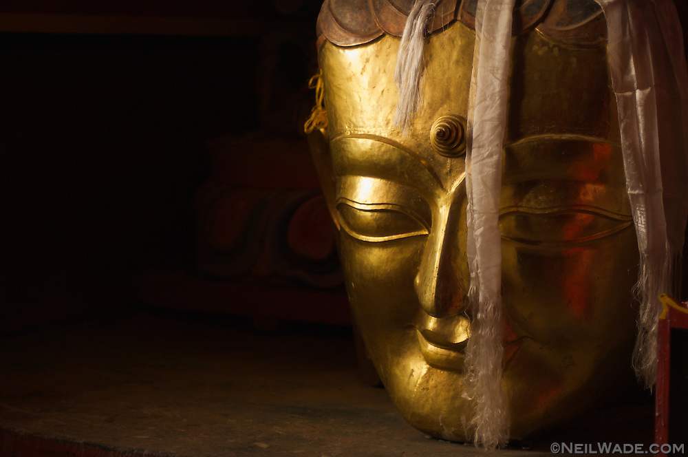 A large carving of Buddha's head sits on a floor in a monastery near XiangCheng, China.
