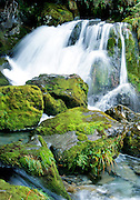Waterfall and mossy boulders on the Routeburn Track, Southern Alps, South Island, New Zealand. In 1990, UNESCO honored Te Wahipounamu – South West New Zealand as a World Heritage Area.