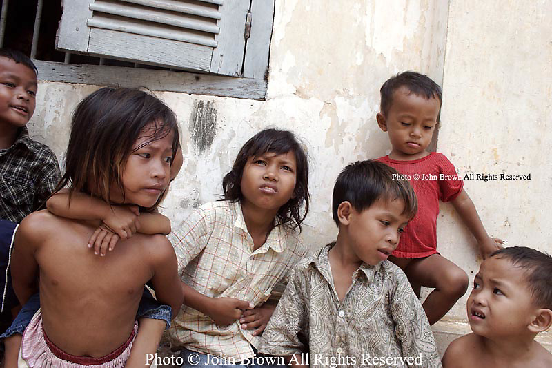 A group of young children too poor to attend school while away their day at a Buddhist temple in Phnom, Penh, Cambodia. The children are residents of an adjacent squatter's slum that is located less than one block from Phnom Penh's main tourist strip. This group is among the nearly five-million Cambodians (about 35%) that The World Bank estimates exists on roughly 2000 riels ($.50 USD) per day.