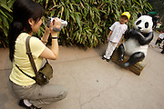 Beijing Zoo. The Great Pandas are the undisputed stars. Parents taking souvenir photos of their kids with a plastic Panda.