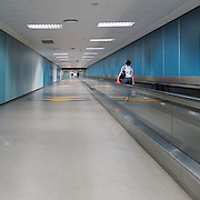 Woman on moving walkway in airport terminal hallway