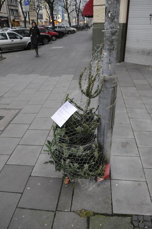 An einen Laternenmast ist ein kleiner Weihnachtsbaum im Netz angelehnt und trägt einen Zettel mit dem Text  : ZUM MITNEHMEN FROHES WEIHNACHTSFEST - VIEL FREUDE DAMIT   | a christmas tree as a gift from  someone to take away for free   |