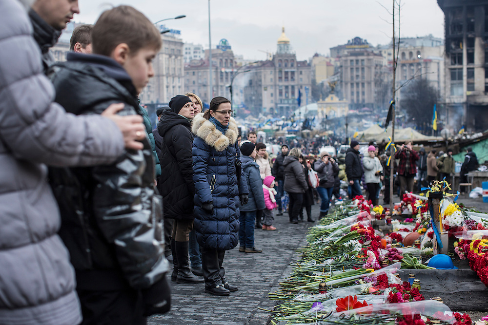 KIEV, UKRAINE - FEBRUARY 23: People pay their respects at a memorial to anti-government protesters killed in chashes with police on Independence Square on February 23, 2014 in Kiev, Ukraine. After a chaotic and violent week, Viktor Yanukovych has been ousted as President as the Ukrainian parliament moves forward with scheduling new elections and establishing a caretaker government. (Photo by Brendan Hoffman/Getty Images) *** Local Caption ***