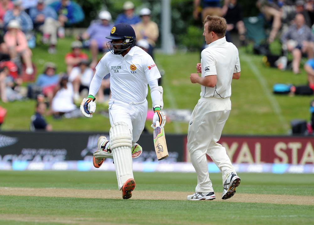 Sri Lanka's Dimuth Karunaratne runs pass New Zealand's Neil Wagner on day two of the first International Cricket Test, University Cricket Oval, Dunedin, New Zealand, Friday, December 11, 2015. Credit:SNPA / Ross Setford