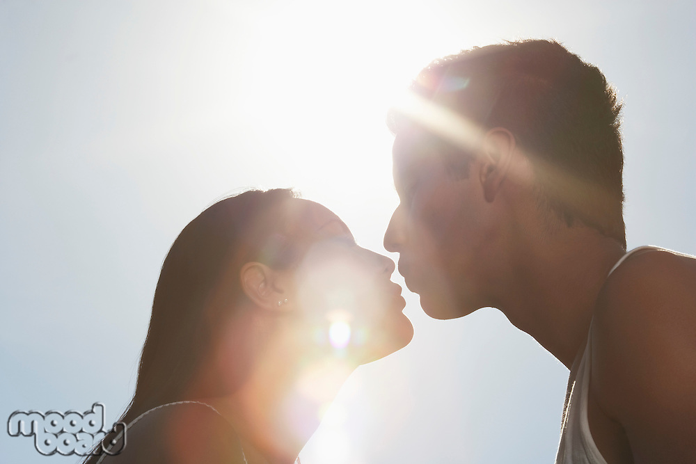 Couple kissing outdoors in sunlight profile