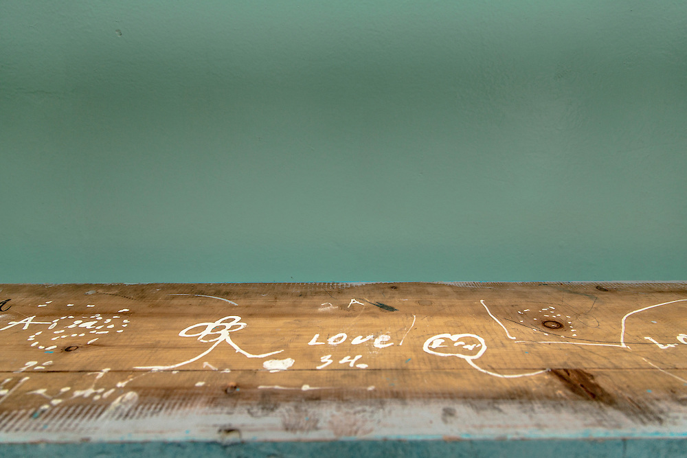 The English word Love was written on the bottom of a bench that sits stacked upside down at the Bulgan County School a boarding school in Bulgan, Mongolia. Like most schools the Bulgan County School uses this time to refurbish the facilities and furnishings.  © 2012 Tom Turner Photography.