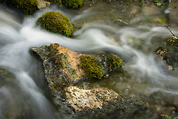 Stock photo of water flowing around rocks in the Llano River in the Texas Hill Country