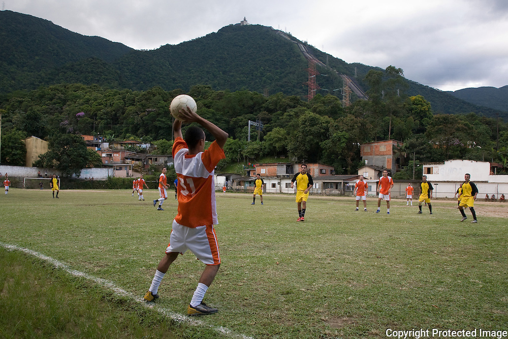 Throw-in during a football game in front of the jungle and water pipelines