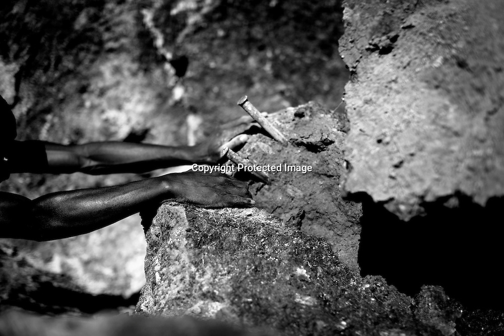 Workers dig mostly by hand in an unregulated quarry for stones to be used for construction outside of Nairobi, Kenya June 5, 2008. A building and construction boom has shot up the demand for building materials, leading to high demand for building stones, ballast and sand. A delay in the review of a Kenyan mining Act has led to the proliferation of new and unregulated quarrying activities in forrest areas and private farm land. According to the National Environmental Management Authority (Nema), of the hundreds of quarries operating in central Kenya only two private quarries conduct an annual audit or have met the country's environments assessment impacts (EAI) requirements. PHOTO BY KEITH BEDFORD