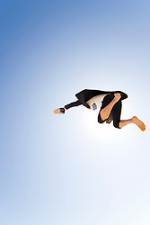 Businessman jumping mid air holding shoes