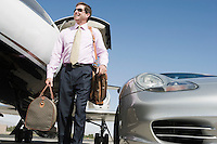 Mid-adult businessman in front of car and airplane.
