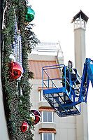Rob Campbell scans the large wreath hanging on the front of The Coeur d'Alene Resort parking structure Friday as he puts the finishing touches on the decoration for the evening's holiday parade and lighting ceremony.