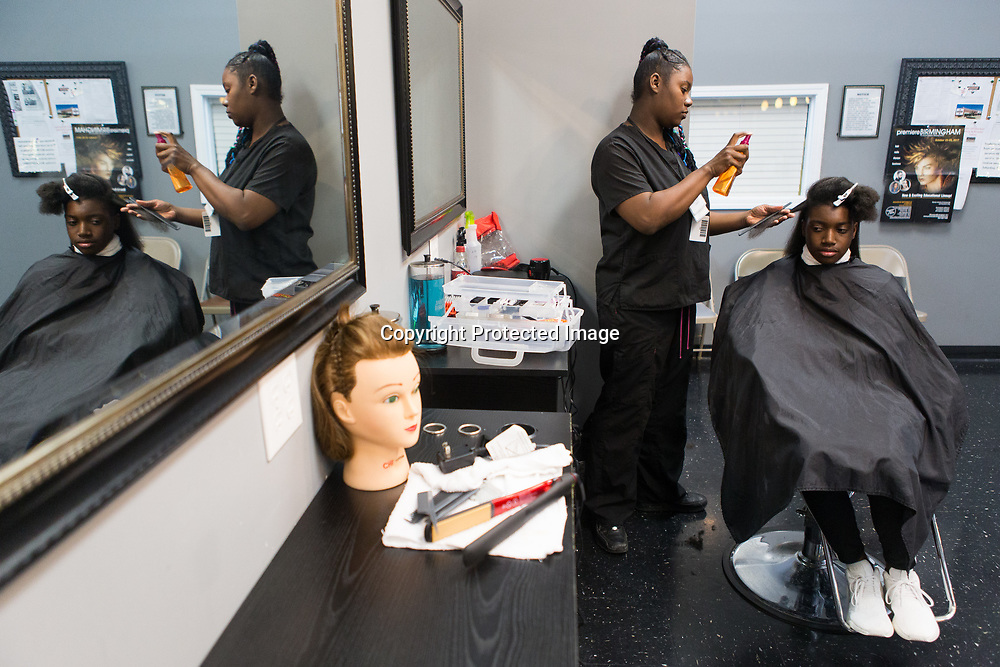 Student Erica Randle flat irons Chandler Bogan's hair Thursday night during the weekly free haircut night at the Tupelo Academy of Cosmetology. Randle is very close to graduating from the school's night program. Tupelo Academy of Cosmetology is accredited through the National Accrediting Commission of Career Arts and Sciences. They are also registered with the Department of Education.