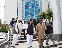 Image ©Licensed to i-Images Picture Agency. 27/06/2014. Morden, United Kingdom. British Muslims condemn Isis at Friday prayers in LND Mosque. Worshipers of Ahmadiyya Muslim leave the mosque after Friday prayers at the Baitul Futuh high security mosque in Morden - the largest mosque in western Europe -  as Islamic Caliph condemns ISIS and extremism. Baitul Futuh Mosque. Picture by Daniel Leal-Olivas / i-Images