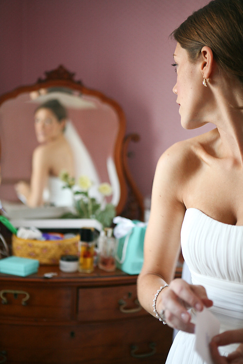 Bride checks her Augusta Jones dress out in the mirror before her Maine Fall Wedding.