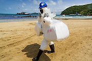 02 AUGUST 2013 - KOH SAMET, RAYONG, THAILAND: A worker carries absorption pads down Ao Prao beach while working to clean up an oil spill that fouled the beach Monday. About 50,000 liters of crude oil poured out of a pipeline in the Gulf of Thailand over the weekend authorities said. The oil made landfall on the white sand beaches of Ao Prao, on Koh Samet, a popular tourist destination in Rayong province about 2.5 hours southeast of Bangkok. Workers from PTT Global, owner of the pipeline, up to 500 Thai military personnel and volunteers are cleaning up the beaches. Tourists staying near the spill, which fouled Ao Prao beach, were evacuated to hotels on the east side of the island, which was not impacted by the spill. Officials have not said when Ao Prao beach would reopen. PTT Global Chemical Pcl is part of state-controlled PTT Pcl, Thailand's biggest energy firm.    PHOTO BY JACK KURTZ