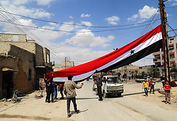 April 14, 2018 - Douma, Syria - Syrians raise a big Syrian national flag in Damascus' eastern Douma district, Syria. The Russian military police and Syrian police forces started deploying in all of Douma in accordance with the deal reached on April 8, under which the Syrian official institutions will return to Douma.  (Credit Image: © Ammar Safarjalani/Xinhua via ZUMA Wire)