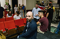 """NAPLES, ITALY - 30 JULY 2018: Roberto Saviano (center), an Italian journalist, writer and essayist is seen here with the young actors of the collective """"Nuovo Teatro Sanità"""" (New Sanità Theatre) in the Sanità neighborhood, in Naples, Italy, on July 30th 2018.<br /> <br /> In 2017 the 17-year-old innocent victim Genny Cesarano was shot and killed by stray bullet  in cross fire between 2 rival gangs vying for territorial control in the Sanità neighborhood.<br /> The  isolation of the neighborhood Sanità over the years provided an ideal location for the Camorra to expand their illicit activities and profit from soaring unemployment rates and economic instability,<br /> <br /> After the first death threats of 2006 by the Casalese clan , a cartel of the Camorra, which he denounced in his exposé and in the piazza of Casal di Principe during a demonstration in defense of legality, Roberto Saviano was put under a strict security protocol. Since 2006 Roberto Saviano has lived under police protection.<br /> <br /> Saviano's latest novel """"The Piranhas"""", which tells the story of the rise of  a paranza (or Children's gang) and it leader Nicolas, will be released in the United States on September 4th 2018."""