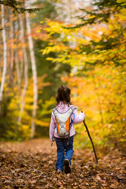 A young girl (age 6) hikes on the Lincoln Woods Trail in New Hampshire's White Mountain National Forest.
