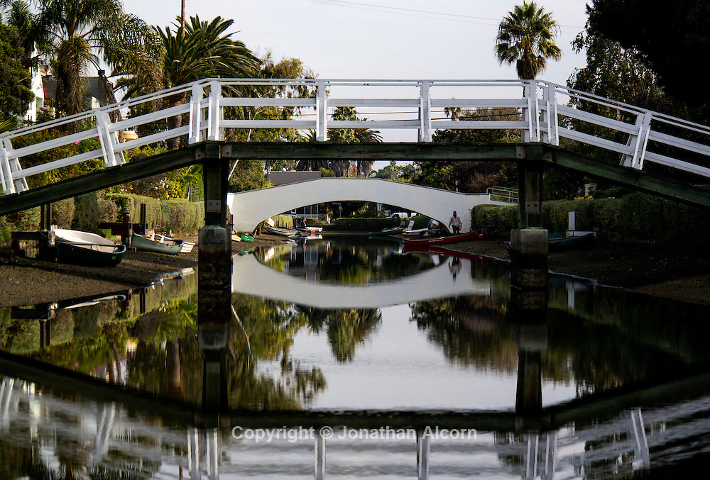 Bridges reflect in the waters of the Venice Beach canals. The Venice Canal Historic District is a district in the Venice section of Los Angeles, California. The district is noteworthy for its man-made canals built in 1905 by developer Abbot Kinney as part of his Venice of America plan.