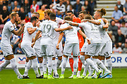 Leeds United players, including Leeds United defender Liam Cooper (6), huddle before kick-off during the EFL Sky Bet Championship match between Wigan Athletic and Leeds United at the DW Stadium, Wigan, England on 17 August 2019.