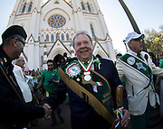 Grand Marshal Hugh Coleman, center, walks back to the parade after receiving a blessing from Bishop Gregory J. Hartmayer of the Diocese of Savannah during the start of the 191st St. Patrick's Day parade, Tuesday, March 17, 2015, in Savannah, Ga. (AP Photo/Stephen B. Morton)