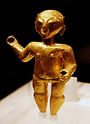 Standing figure.  Ecuador or Colombia, Tolita-Tumaco. 1st-4th century, hammered gold.  Three dimensional figures in the Tolita-Tumaco style are among the most unusual Precolumbian gold objects.  The figure displayed here is distinguished by its decorated nose ornament.  The Tolita-Tumaco style area is located on the Ecuador-Colombian border along the Pacific coast.