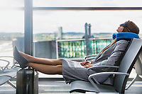 Portrait of young businesswoman sleeping with her head pillow and eye mask while waiting for boarding in airport