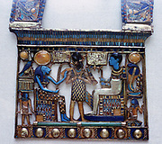 Pectoral jewel from tomb of Tutankhamun showing Ptah, creator of universe and patron of craftsmen, and his consort, Sekhmet, lion-headed goddess of war either side of Tutenkhamun in regalia of Pharaoh.