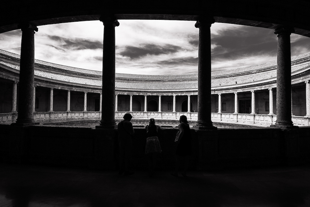 Columns of the Charles V Palace and tourists at Alhambra, Granada, Spain.