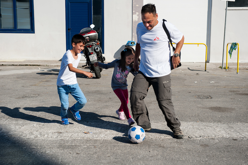MSF doctor Dimitris Giannousis playing football with refugee kids at the port of Mytiline.