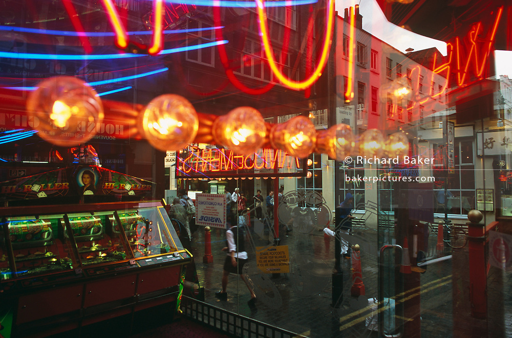 Seen through the window of an amusement arcade in London's Gerrard Street, Chinatown, we see the colourful neon lights that garishly shine from behind the glass. Beyond is the hustle and bustle of daily life in this famous street of London's Chinese community. We are slightly confused as to what is inside and what is out. We see the Georgian architecture reflected from behind and to the left is a slot-machine game called Hi-Roller which suggests the use of dice in this gambling activity. Passers-by can be seen outside, making their way past the many restaurants and businesses. In the middle of the scene is a yellow sign positioned by the Metropolitan Police warning against pickpockets as this area of the West End is known for petty crime.