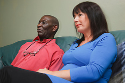 Elderly black man with white woman carer at home watching television