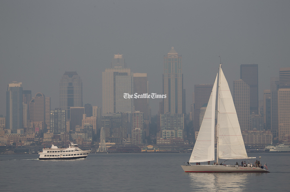 A sailboat and ferry pass by a hazy Seattle skyline, seen from the Alki Trail, as smoke, brought over by winds from the Eastern Washington wildfires, affects air quality and visibility in the area on Sunday, Aug. 23, 2015. <br /> <br /> Lindsey Wasson / The Seattle Times