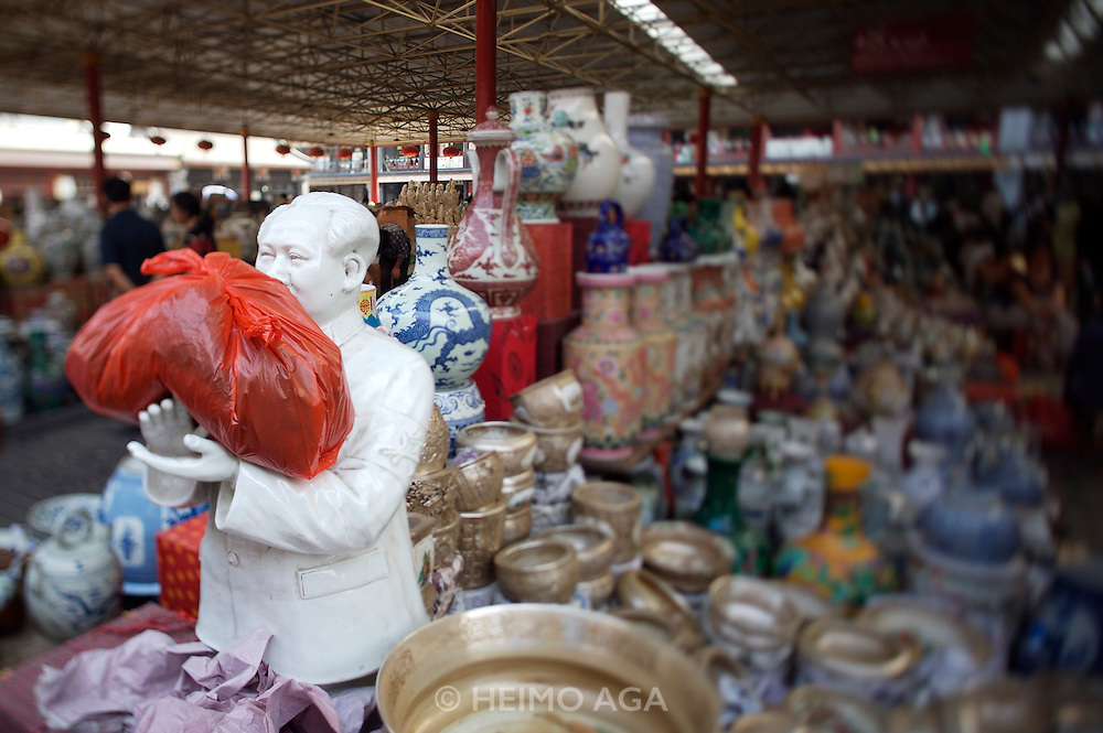 Panjiayuan weekend market. Porcelaine and ceramics. Porcelaine bust of Chairman Mao used to hold a red plastic bag.