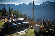 Beñat, Nathalie and Oihu have breakfast while Kemen plays drums with an impvrovised drum set.  Village of Brontallo (Switzerland) July 03, 2014. Beñat and Nathalie spend two months (July and August) on Spulüi, at 1.900 meters, taking care of goats and making cheese. Their children Kemen (7 years old) and Oihu (18 months) are with them. (Gari Garaialde / Bostok Photo)
