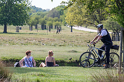 © Licensed to London News Pictures. 26/04/2020. London, UK. A Police officer speaks to a couple while out patrolling in Richmond Park. Members of the public go out to enjoy the warm weather in Richmond Park which looked busy today during lockdown where temperatures are expected to reach 21c. London has seen an increase in traffic and busier High Streets as more shops and cafes start to open up during the coronavirus pandemic crisis. Photo credit: Alex Lentati/LNP