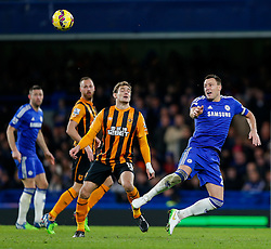 John Terry of Chelsea heads the ball as Nikica Jelavic of Hull City challenges a- Photo mandatory by-line: Rogan Thomson/JMP - 07966 386802 - 13/12/2014 - SPORT - FOOTBALL - London, England - Stamford Bridge - Chelsea v Hull City - Barclays Premier League.