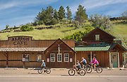 Family biking in downtown Albion near historic Cafe and Saloon buildings in Albion, Idaho. MR