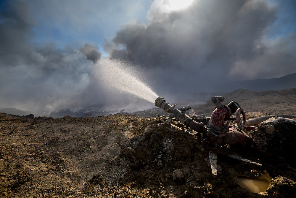 A single hose is trained on a burning pit of oil during firefighting efforts. The water comes from the nearby Tigris River. Qayyara, Iraq. Nov. 23, 2016. (Photo by Gabriel Romero ©2016)