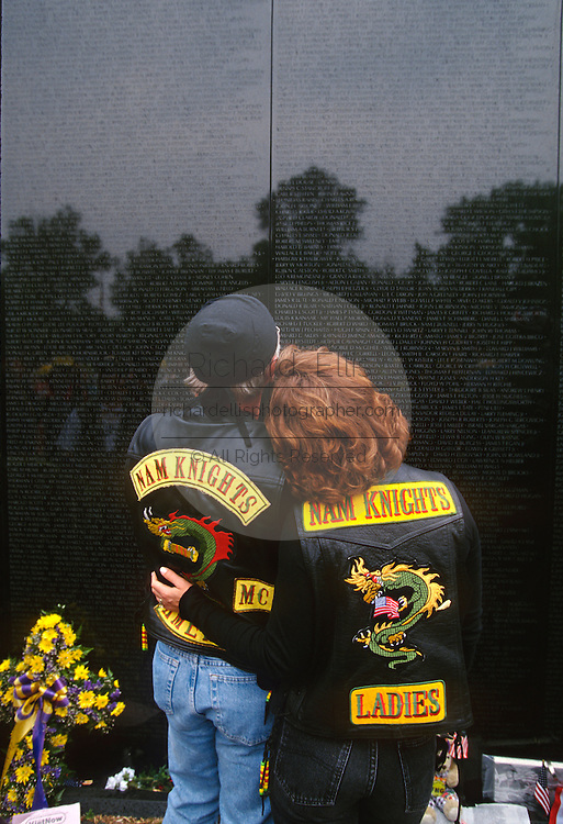 A couple pauses for a moment at the Vietnam Veterans Memorial wall November 11, 1996 in Washington, DC.