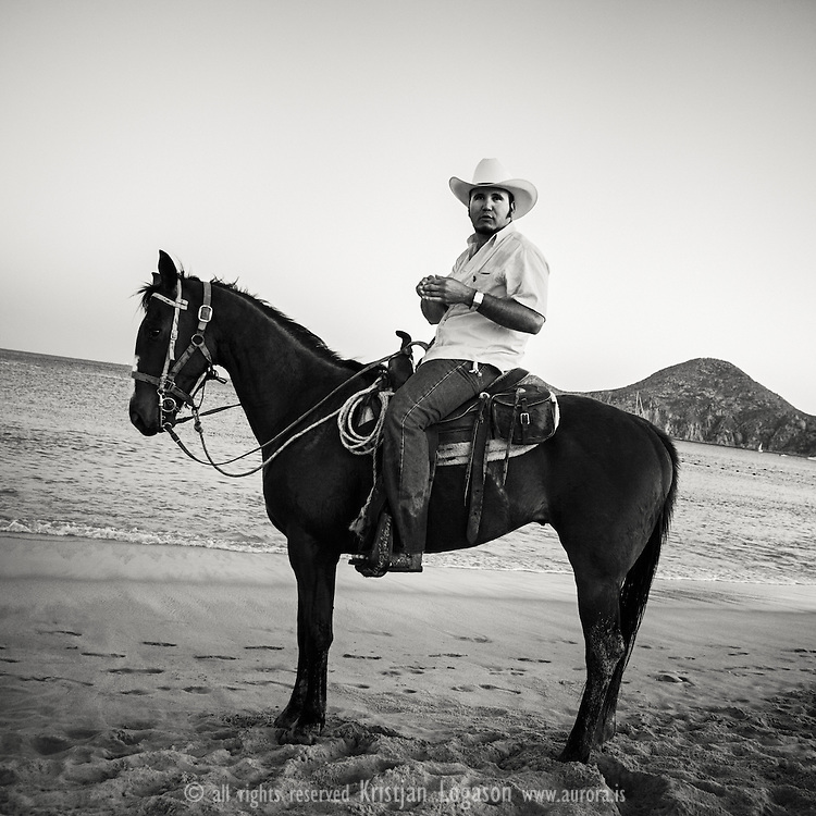 Horse rider cooling of his horse in the cold see at Cabo san Lucas Baja California Mexico