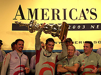 ALINGHI AND EX NEW ZEALAND WINNER RUSSELL COUTTS AFTER BEING SO RELUCLENT TO LIFT THE CUP LIFTS IT FOR THE FIRST TIME AT THE PRESS CONFERENCE AFTER A LOT OF PERSUASION.