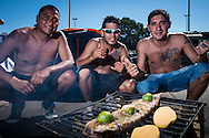 Martin, Maxi and Diego from Mendosa, Argentina, sit around a cooking fire with a large steak sizzling away at the site set up for football fans who had nowhere to stay but the tents, campervans, cars and caravans that they had bought with them. The site, at the Terreirao Do Samba, Rio de Janeiro, Brazil, was arranged by the city government once they realised the number of fans in this situation was significant and rather than having them scattered about the sity they offered secure, enclosed accommodation with sanitation and water. The majority of fans at the site were Argentinian but there were also people from Chile, USA, Uruguay and Colombia. Photo by Andrew Tobin/Tobinators Ltd