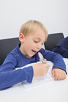 Little boy writing in book at table