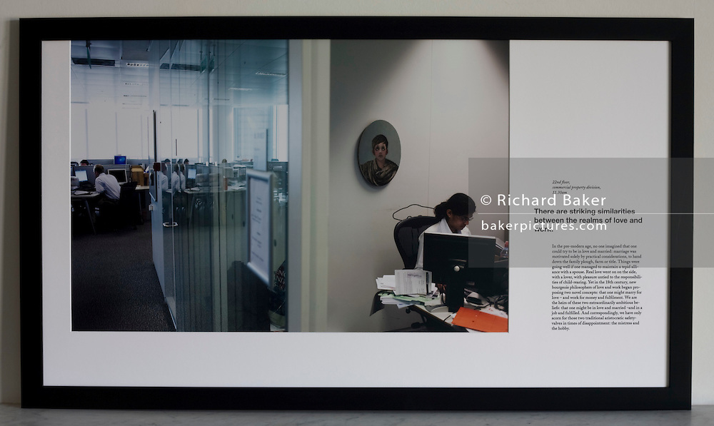 A casually-dressed accountant works in a cluttered office cubicle in an auditing company's London headquarters.<br />
