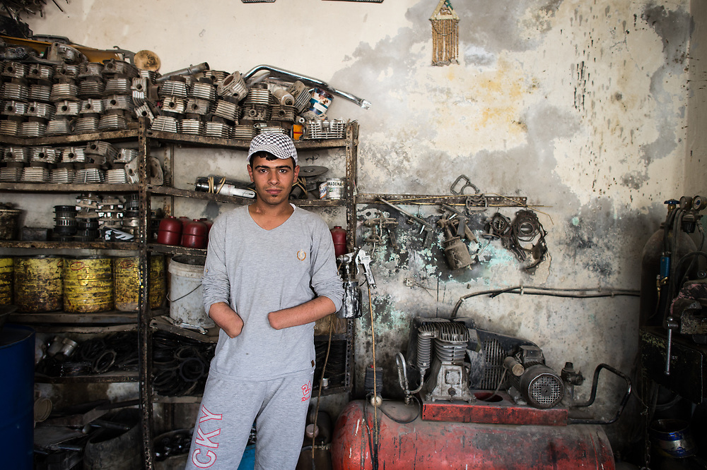 19-year-old Mustafa is standing in the car workshop of his uncle  in Kobanê. One year ago, Mustafa fought with the YPG against ISIS, who were advancing against Kobanê. He was heavily injured by an explosive device and lost both hands. Kobanê, (Ayn al-Arab) Syria, June 21, 2015